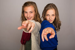 Two young girls pointing their fingers at camera. Two kids pointing fingers at the camera Stock Photo