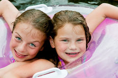Two young girls in pool with float Royalty Free Stock Image