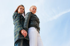Two young girls portrait over sky. Bottom view Royalty Free Stock Photos