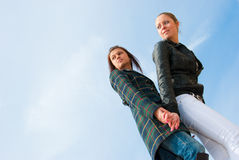 Two young girls portrait over sky. Bottom view Stock Images