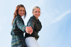 Two young girls portrait over sky. Bottom view Royalty Free Stock Photography