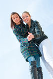 Two young girls portrait over sky. Bottom view Royalty Free Stock Image