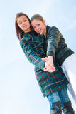 Two young girls portrait over sky. Bottom view Royalty Free Stock Images