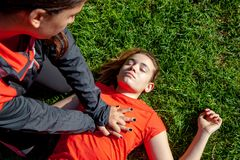 Two young girls practicing cardiopulmonary resuscitation manoeuvres in an open-air park. Two young girls dressed in sport clothes practicing cardiopulmonary stock images