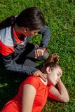 Two young girls practicing cardiopulmonary resuscitation manoeuvres in an open-air park. Two young girls dressed in sport clothes practicing cardiopulmonary stock photography
