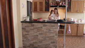 Two young girls prepare Breakfast in the kitchen. Two young girls prepare Breakfast in the kitchen at home, they open the refrigerator and take out the products stock video footage