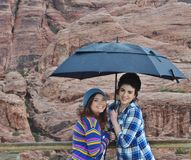 Two young girls in the rain. Two young, attractive girls holding an umbrella standing in front of red rocks in the rain Royalty Free Stock Image
