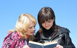 Two young girls reading a book. On a background of blue sky Stock Image