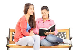 Two young girls reading a book seated on wooden bench. Isolated on white background Royalty Free Stock Images