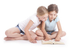 Two young girls reading a book together. In studio with white background Royalty Free Stock Images
