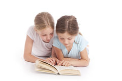 Two young girls reading a book together. In studio with white background Stock Image