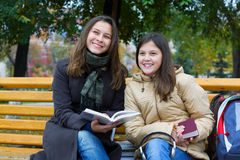 Two young girls reading in the park. Stock Photos