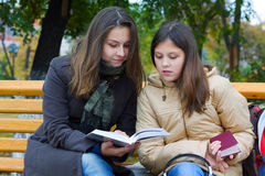 Two young fashion teen girls reading a book in park. Two young fashion teen girls reading a book in city park Stock Photography