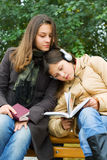 Two young girls reading in the park. Royalty Free Stock Photography