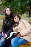 Two young girls reading in the park Royalty Free Stock Photos
