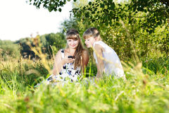 Two young girls reading sms on cell phone on nature. Royalty Free Stock Photo