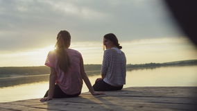 Two Young Girls Relaxing Near River stock video