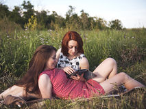 Two young girls on a rest outdoors Royalty Free Stock Image