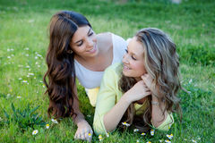 Two young girls resting on the grass. Royalty Free Stock Images