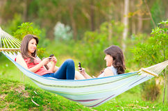 Two young girls resting on a hammock smiling Stock Photos