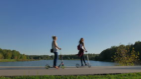 Two young girls riding a scooters along the city pond. Shooting movies in 4K and downscale to Full HD. The shutter speed is 1/50. With the use of ND-filter stock footage