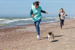 Two girls run with dog. Two young girls run along the sea with the dog Stock Photos