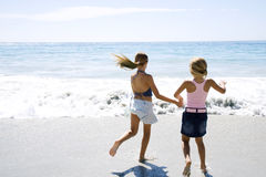 Two young girls running on the beach hand in hand Stock Photo