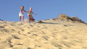 Two Young Girls Running Down Sand Dune Together. Two young girls running down sand dune past camera position.Shot on Canon 5d Mk2 with a frame rate of 30fps stock footage
