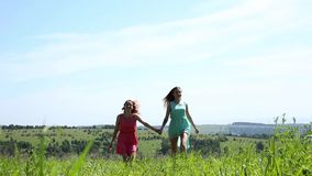 Two young girls are running on a field hand in hand, freedom and relationship concepte.  stock footage