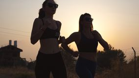 Two young girls running outdoors at sunset. Young athletic women jogging at country road. Female athletes training. Together at nature. Healthy active lifestyle stock video footage