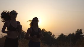 Two young girls running outdoors at sunset. Young athletic women jogging at country road. Female athletes training. Together at nature. Healthy active lifestyle stock footage