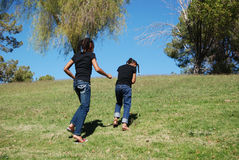 Two young girls running up a hill Royalty Free Stock Photos