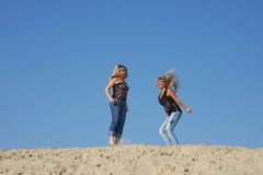 Two young  girls on a sand-pit Stock Photos