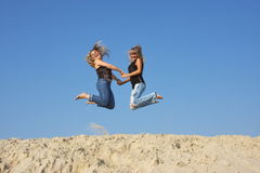 Two young  girls on a sand-pit Stock Images