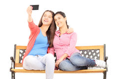Two young girls seated on bench taking picture of themselves wit Stock Photo