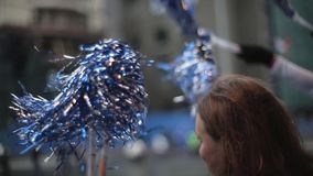 Two young girls shaking in hands blue pom poms in bus. Day. Sport event. Slow motion. Close up stock footage