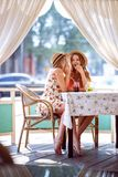 Two young girls share a secret in the ear sitting in a cafe royalty free stock images