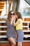 Two young girls share secrets. Two cute women,brunettes with long hair ,dressed in a striped summer dress and a striped skirt and a yellow t-shirt,a good friend Stock Photography