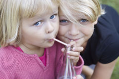 Two young girls sharing. Two blond girls sharing a drink Royalty Free Stock Photo