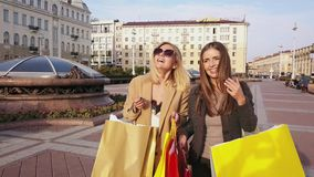 Two young girls with shopping bags walking in a city. Steadicam shot of happy women with purchase in colorful paper bags. City background. 4k stock video