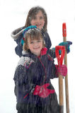 Two Young Girls Shoveling Snow royalty free stock image
