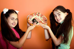 Two young girls show on pizza Royalty Free Stock Photo