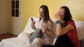 Two young girls sit at home on the couch, on a rainy day watching a Comedy, talking and laughing. Evening, home, comfort stock footage