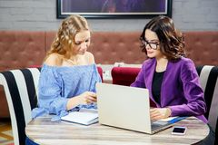 Free Two Young Girls Sitting At The Laptop While Discussing Business Matters Stock Images - 103129354