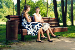 Two young girls sitting on bench in the park enjoying summer and chatting. Stock Image