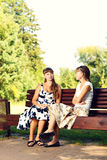 Two young girls sitting on bench in the park enjoying summer and chatting. Royalty Free Stock Image