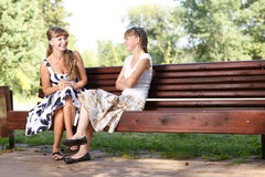 Two young girls sitting on bench in the park enjoying summer, smiling and chatting. Royalty Free Stock Photography