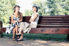 Two young girls sitting on bench in the park enjoying summer, smiling and chatting. Royalty Free Stock Images
