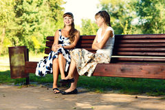 Two young girls sitting on bench in the park enjoying summer, smiling and chatting. Stock Photos