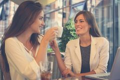 Two young girls sitting in cafe drinking coffee. Two young girls sitting in cafe drinking coffee and having conversation Royalty Free Stock Photo